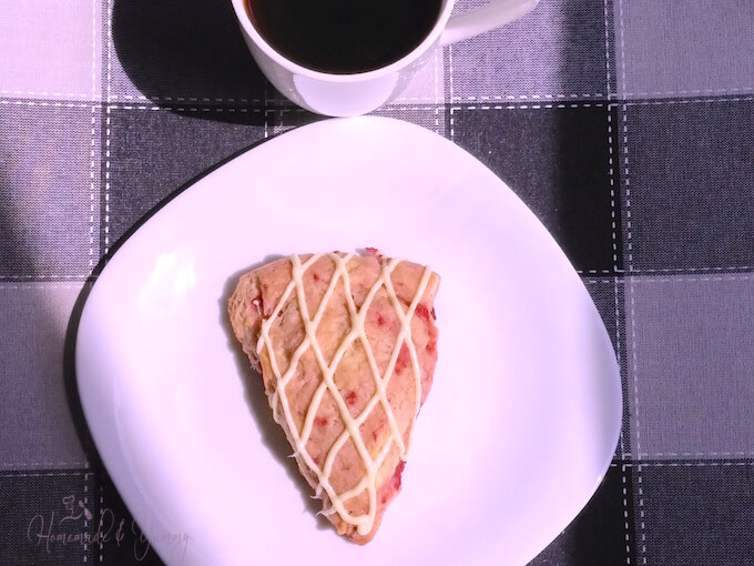 A single strawberry scone on a plate ready to eat.