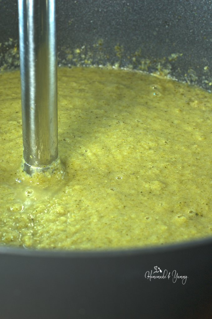 Soup getting blended with an immersion blender.
