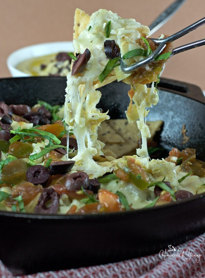 Closeup of Greek nachos in a cast iron skillet.