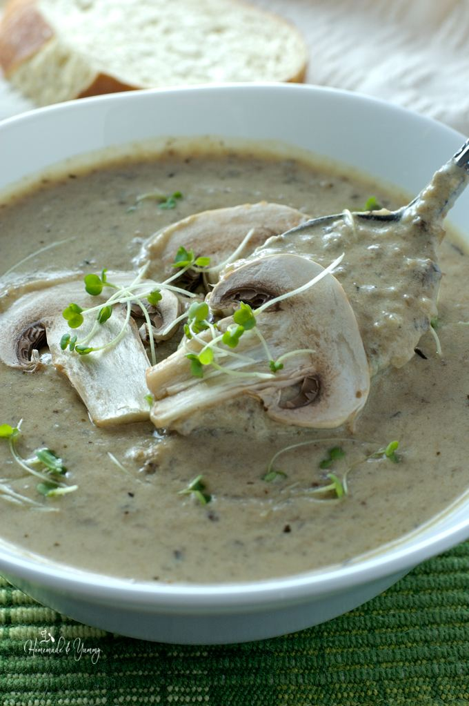 Closeup of soup garnished with slices of fresh mushroom.