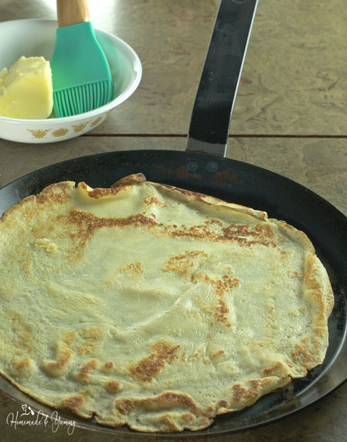 Crepes cooking in a crepe pan.