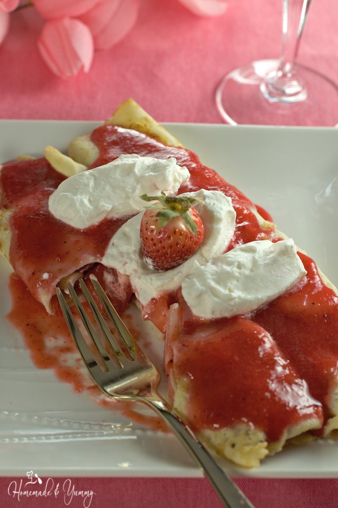 2 strawberry crepes on a plate with a fork.