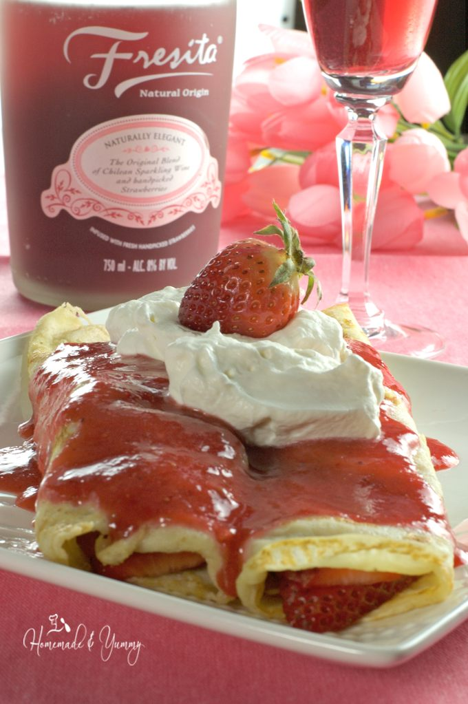 Strawberry crepes on a plate, sparking wine in the background.
