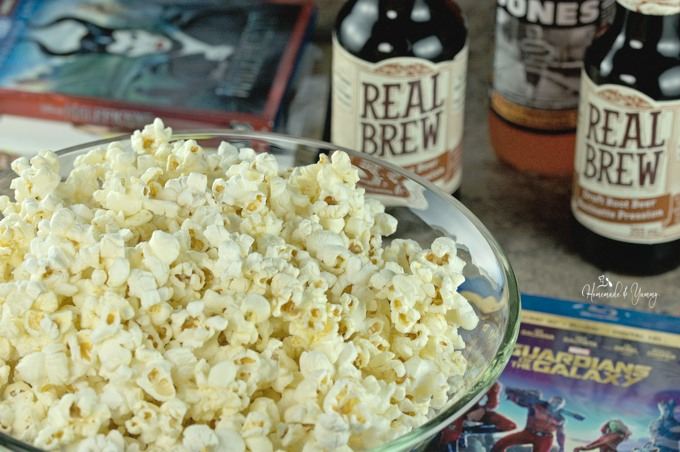 Closeup Maple Bacon Popcorn with movies and beverages in the background.