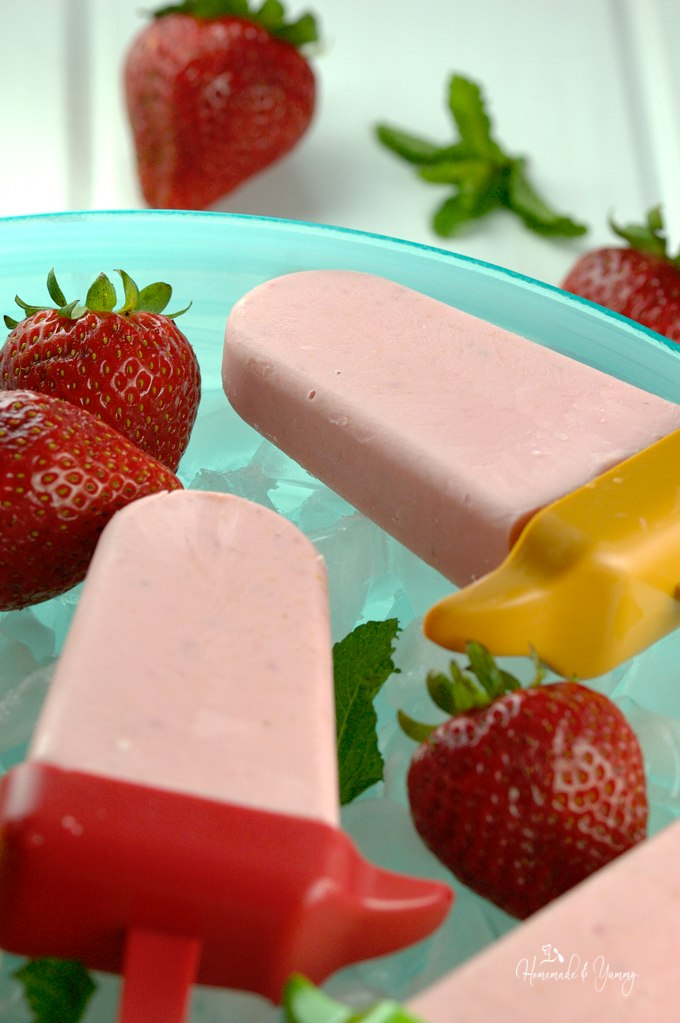 Strawberry Cheesecake Popsicles on a be of ice.