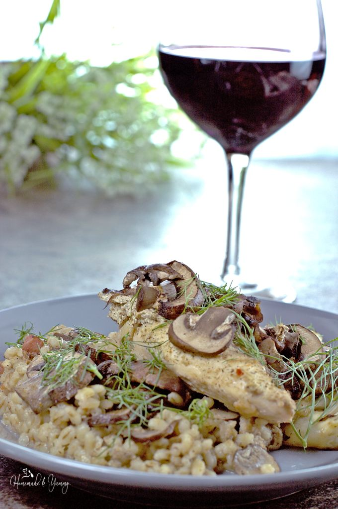 Chicken Mushroom and Barley casserole on a plate, glass of wine in the background.