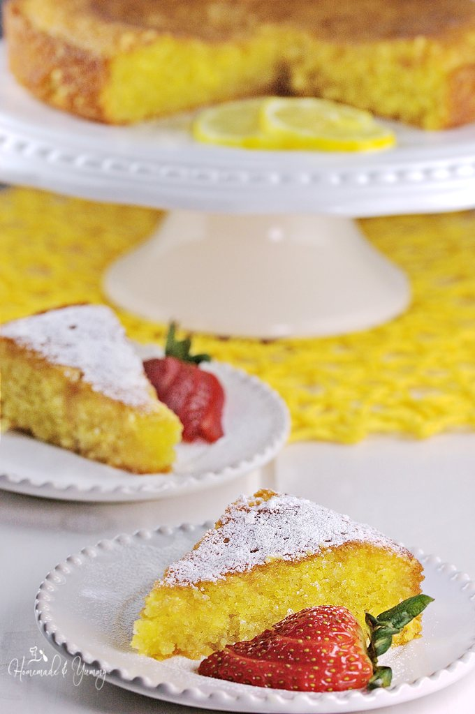 A slice of Lemon Cake on a plate, dusted with icing sugar.