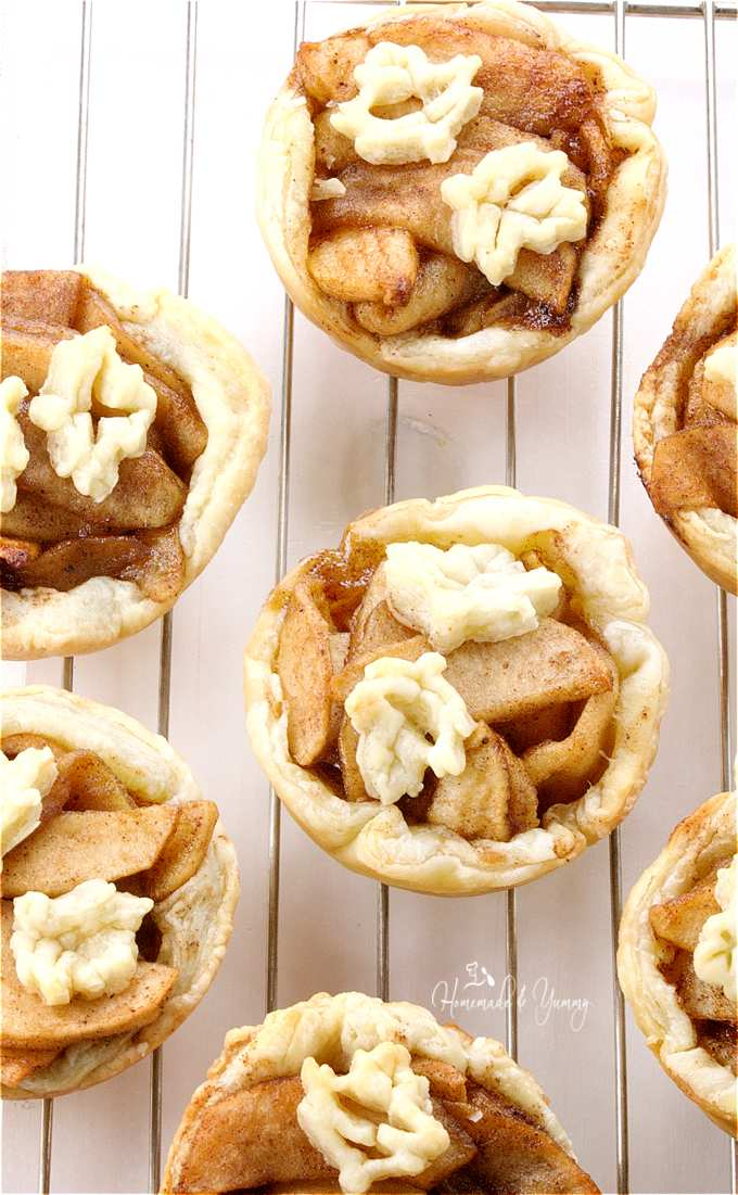 Fresh baked apple tartlets on a cooling rack.