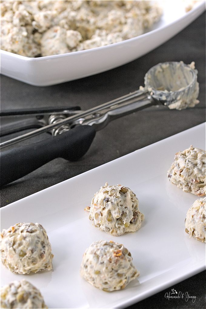 Close up of cream cheese balls getting placed on a plater, mini ice cream scoop in the background with a bowl of lentil mixture.