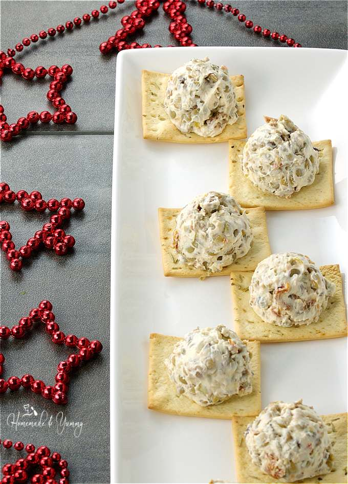 Mini Cream Cheese Balls on a serving tray, Christmas decorations in the background.
