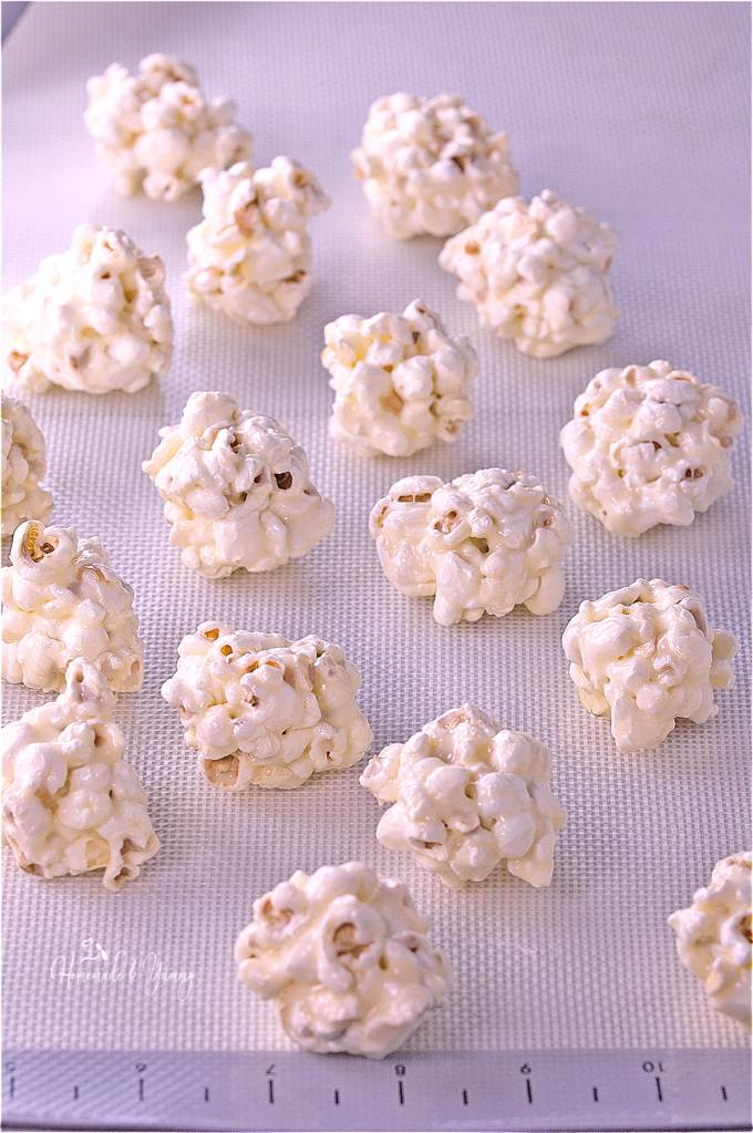 Holiday White Chocolate Mini Popcorn Balls are the perfect addition to any cookie tray. Bite size balls of popcorn, dipped in white chocolate, and decorated with holiday sprinkles. An easy no bake, gluten free treat that makes an awesome food gift too.| homemadeandyummy.com