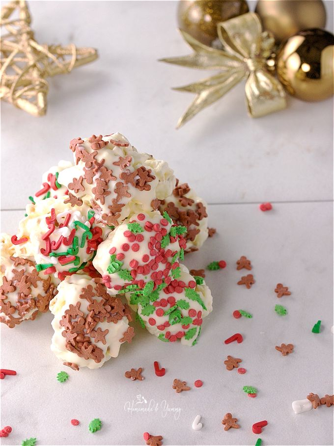 Overhead shot of a pile of popcorn balls, sprinkles scattered around and holiday decorations in the background.