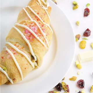 Quick & Easy Festive Holiday Croissants are perfect for weekend brunches. Filled with pistachios, cranberries and drizzled with white chocolate, they represent the colours of the holiday in taste and appearance. | homemadeandyummy.com