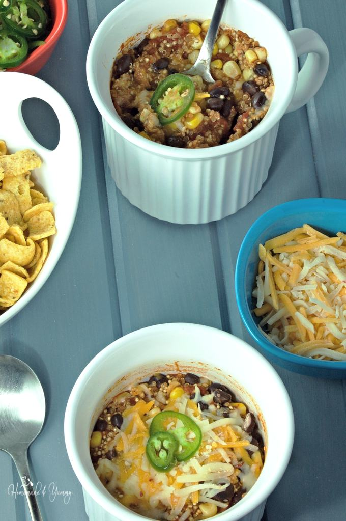 Overhead shot of mini casseroles with grated cheese and corn chips on the side.