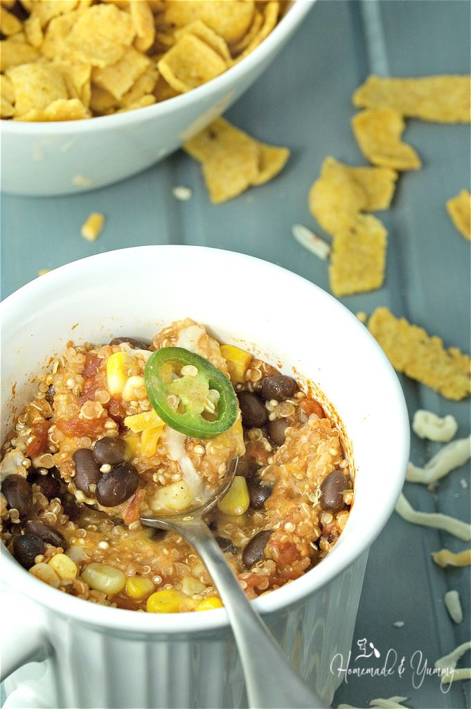 Close up shot of Mexican quinoa casserole in a mug, with a spoon in it, ready to eat.