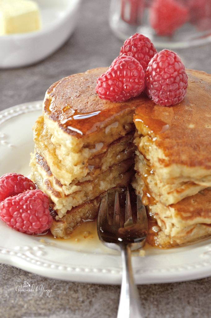 Close up shot of a stack of oatmeal pancakes with a fork, topped with fresh raspberries.