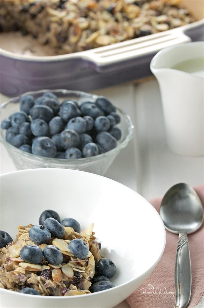 Close up of the breakfast casserole in a bowl, fresh blueberries in the background.