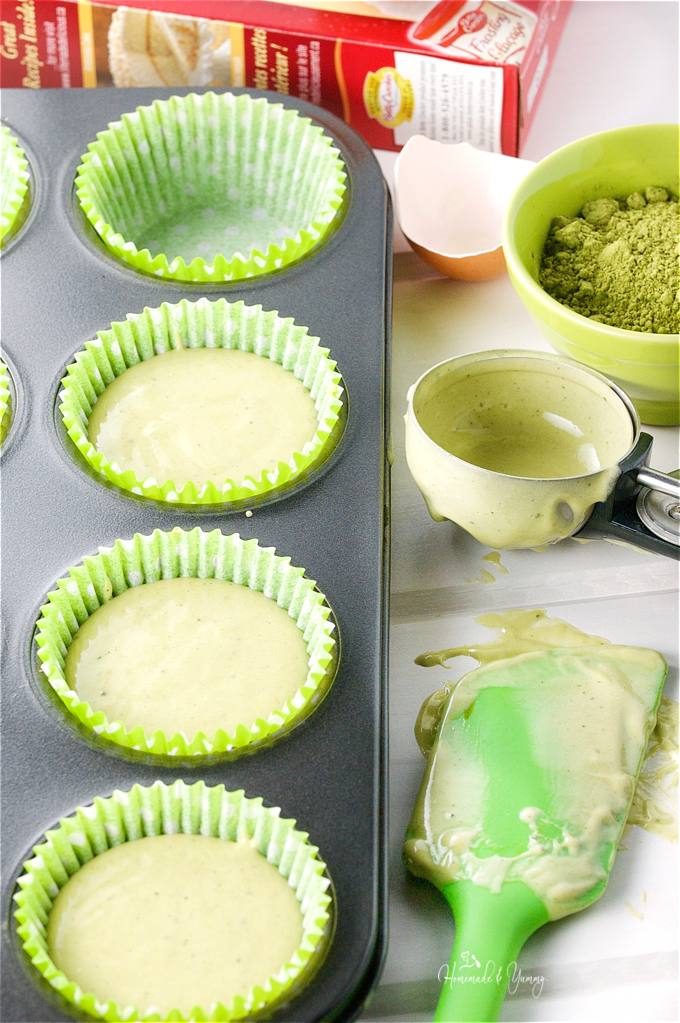Cupcake pan with liners, some filled with the cupcake batter ready to go into the oven.