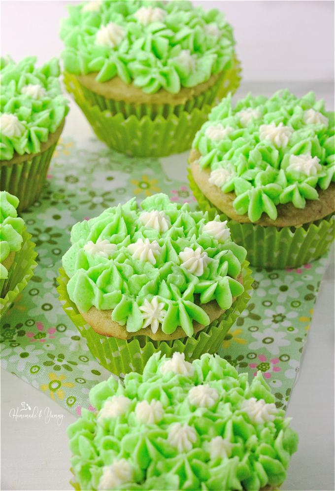Close of decorated vanilla cupcakes on the table with a green floral napkin.