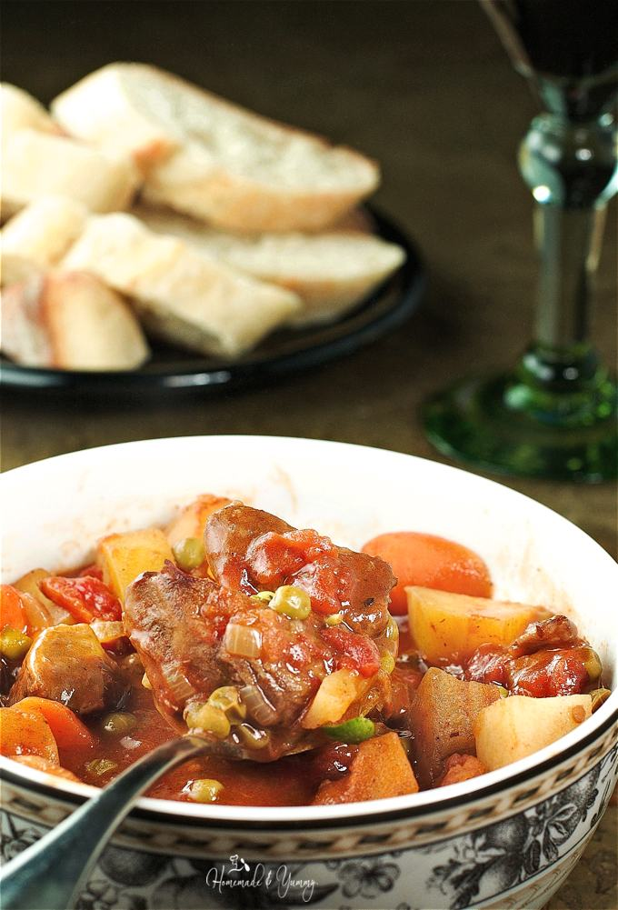Close up of stew in a bowl with a spoon ready to eat, bread in the background.