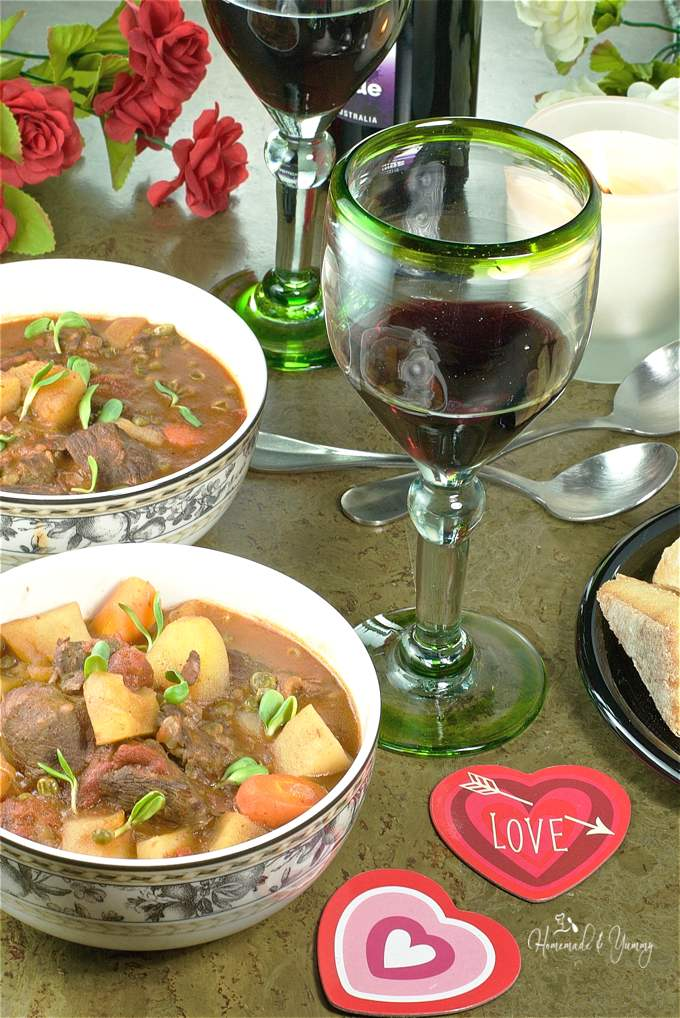2 bowls of stew, 2 glasses of wine, Valentine decorations and flowers in the background ready for a romantic dinner.