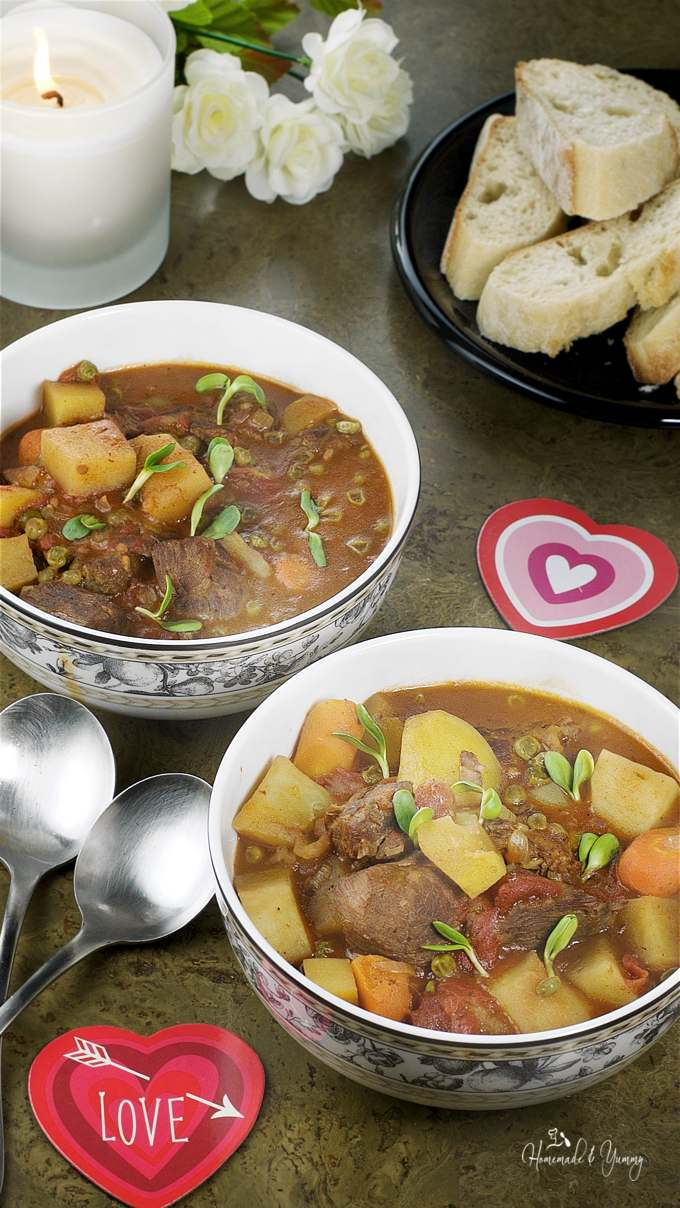 2 bowls of stew with Valentine decorations and a candle in the background, ready for a romantic dinner.