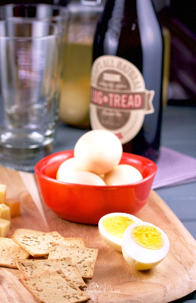 A wooden board containing crackers, cheese, a dish of pickled eggs, and beer in the background.