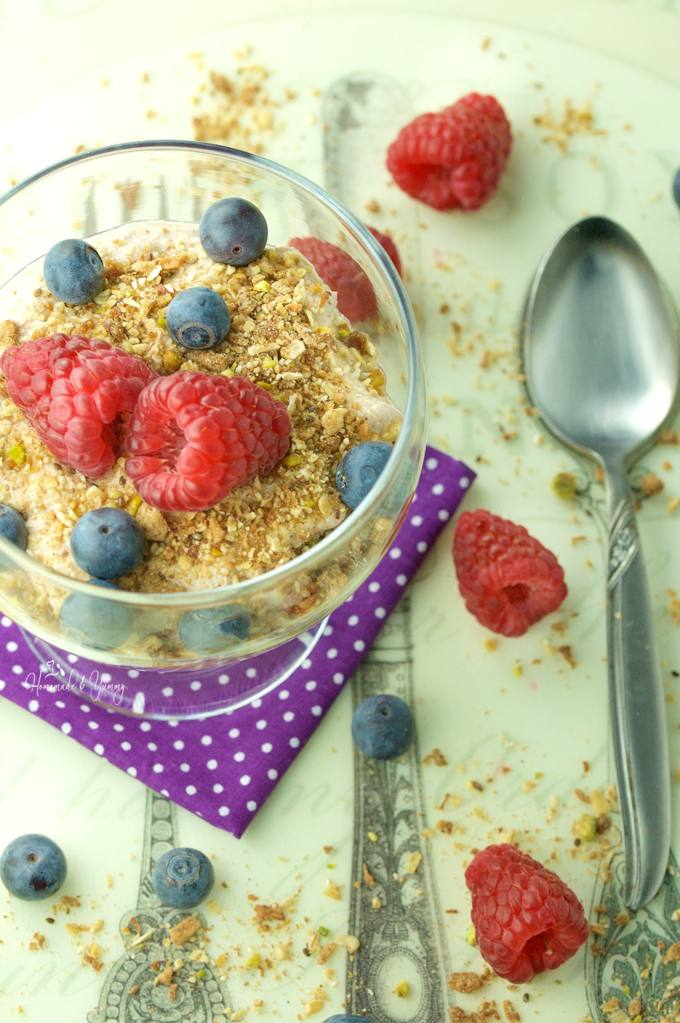 Overhead shot of yogurt is a bowl, topped with granola and fresh blueberries and raspberries, spoon on the side.