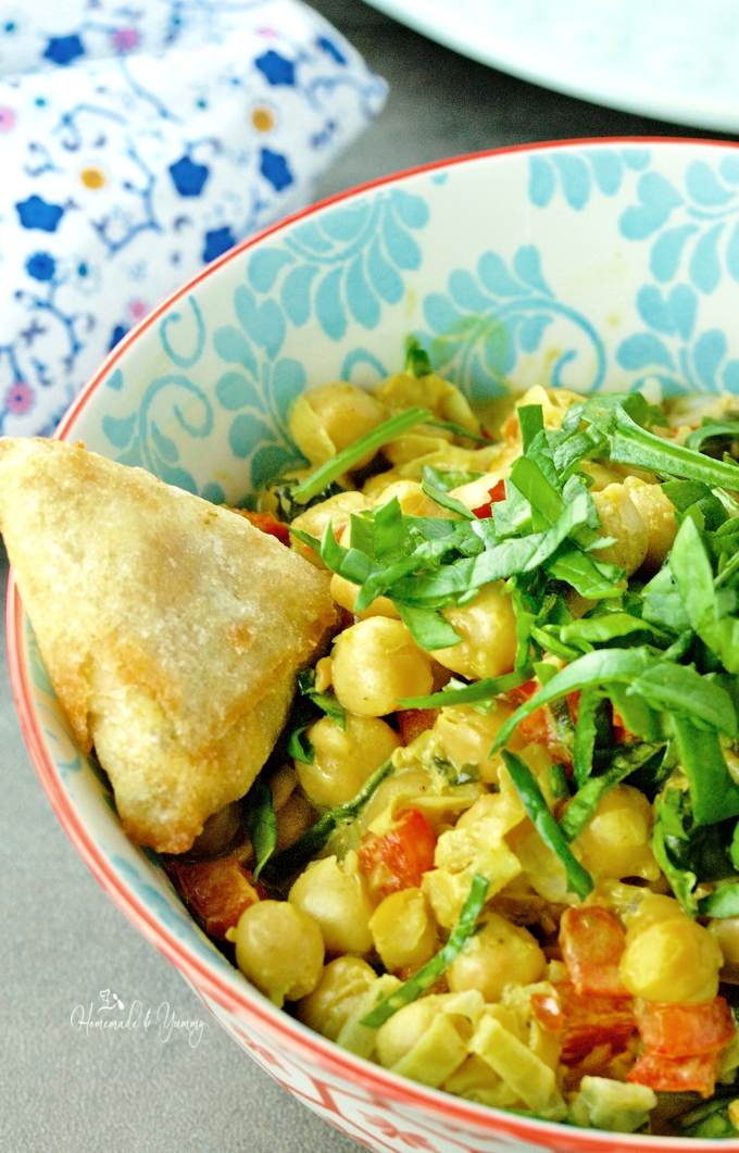 Close up of curry in a bowl with a samosa on the side.