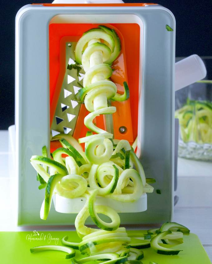 Close up of zucchini noodles coming out of spiralizer.