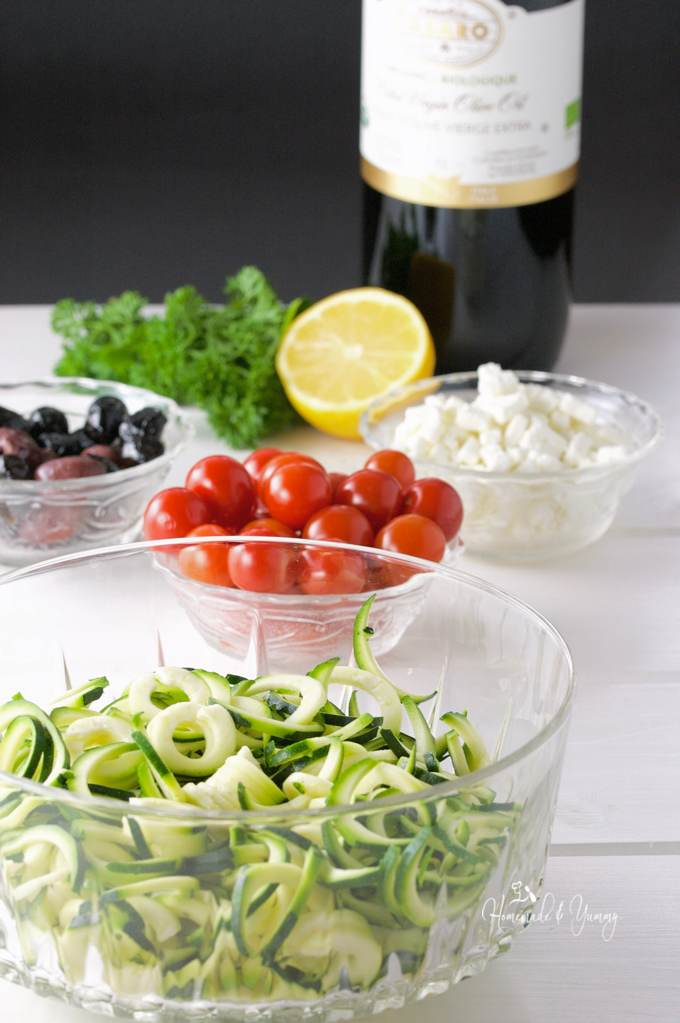 Recipe ingredient, zoodles, tomatoes, feta cheese, olive oil, and olives.