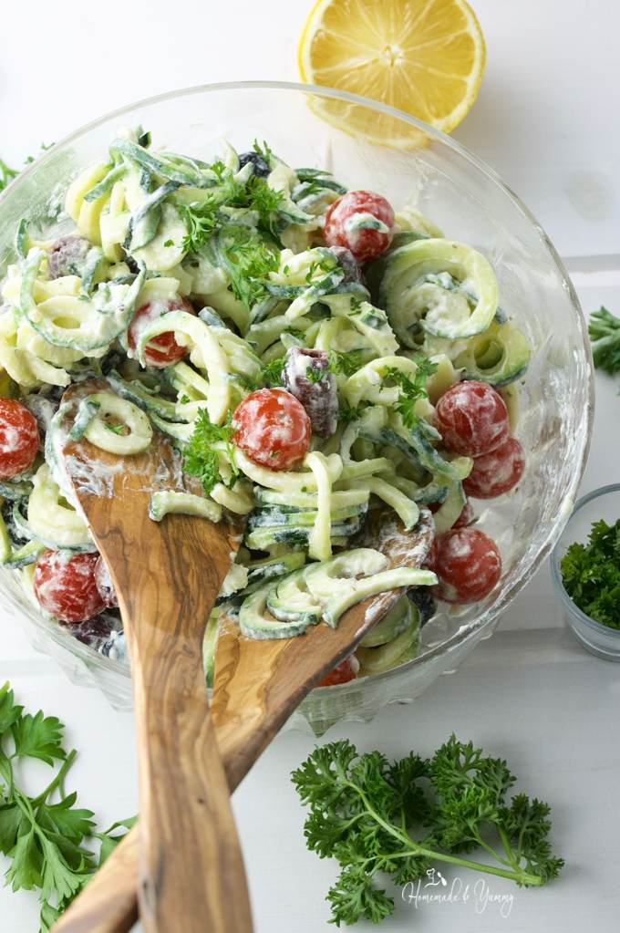 Overhead shot of Zoodle Salad in a large serving bowl with wooden utensils.