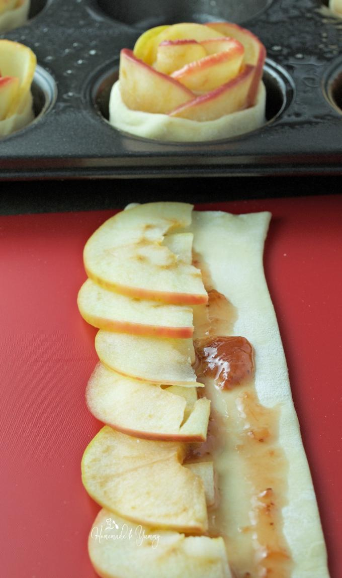 Close of up pastry, sliced apples and jam before being rolled up into a rose.