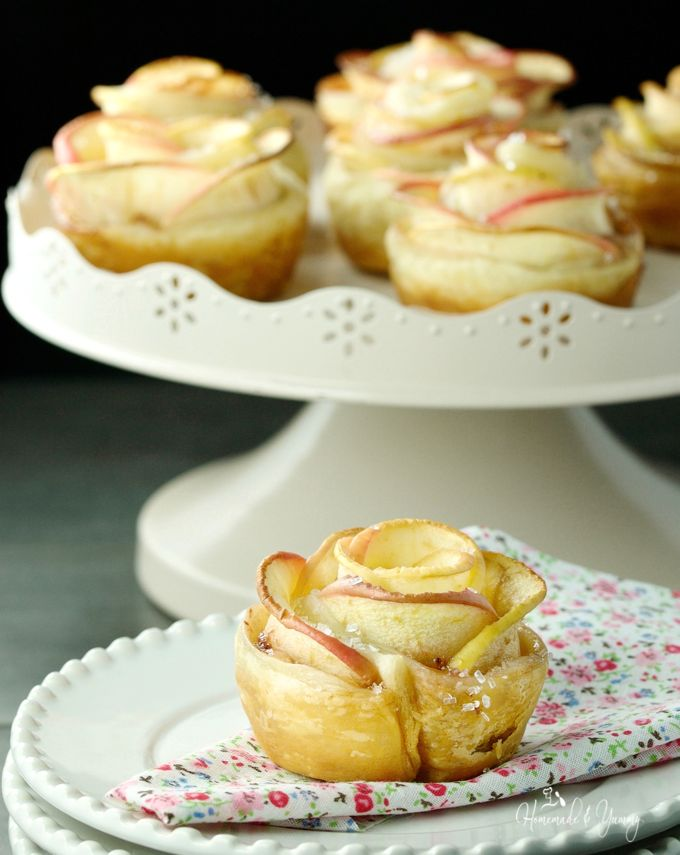 Close up of Apple Roses on a plate with more in the background on a cake stand.