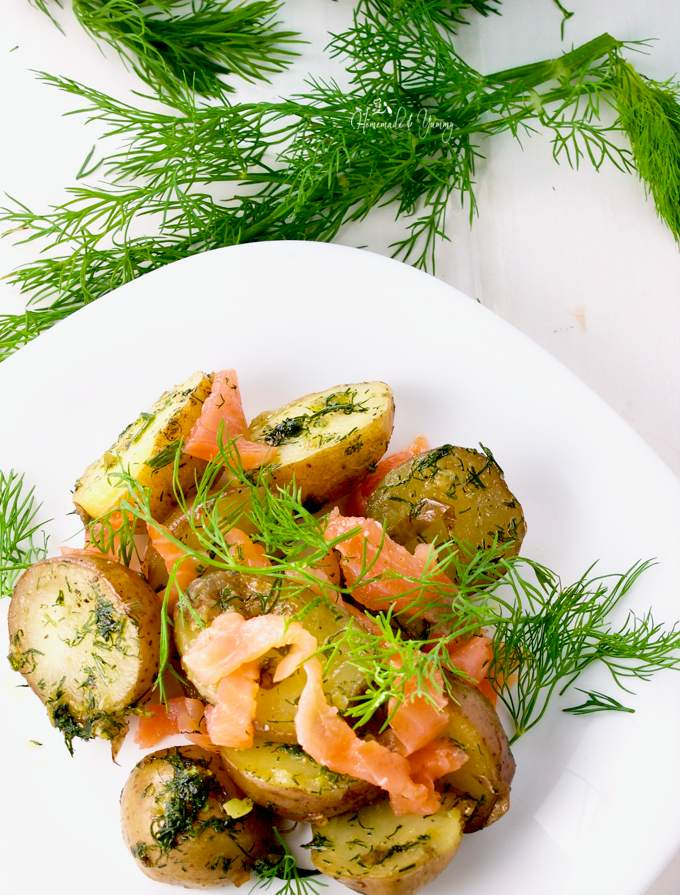 Overhead shot of Warm Potato Salad with Dill & Smoked Salmon in bowl with dill in the background.