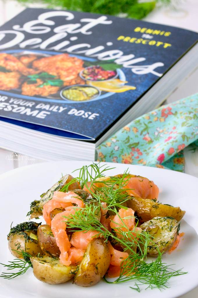 Close up shot of Warm Potato Salad with Dill & Smoked Salmon with the cookbook in the background.