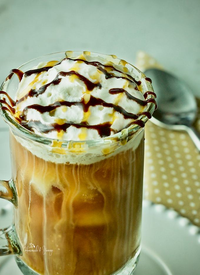 Close up shot of iced coffee in a glass mug with whipped cream and drizzled with chocolate and caramel sauce.