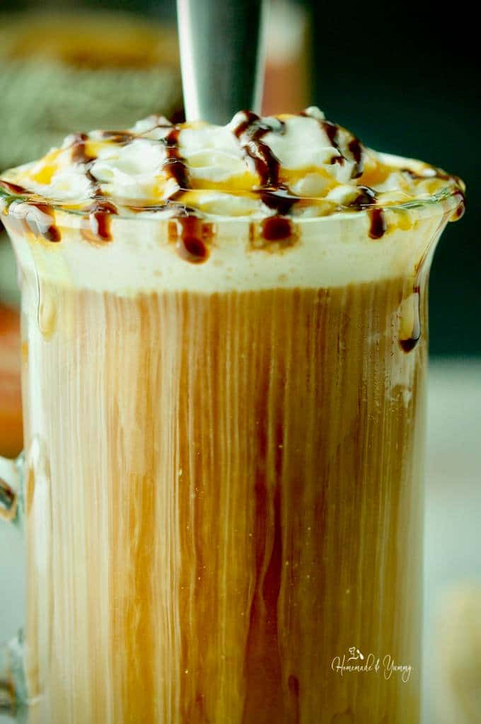 Close up shot of iced coffee in a glass showing the whip cream streaming through to the bottom of the glass.