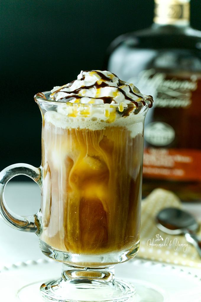 Iced coffee in a glass with whipped cream and drizzle topping. Bourbon bottle in the background.