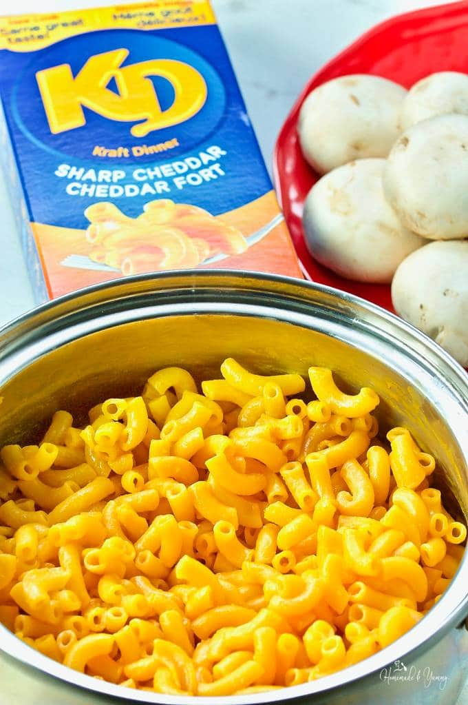 Kraft dinner in a pot with the package and mushrooms in the background.