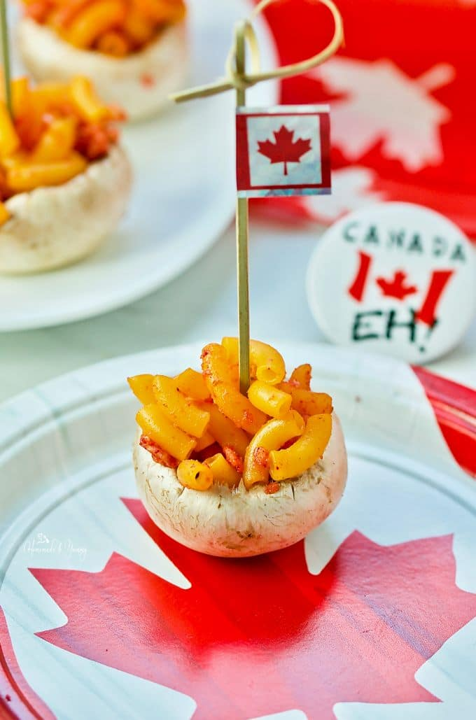 A close up of 1 single mushroom bite on a plate with a Canadian flag.