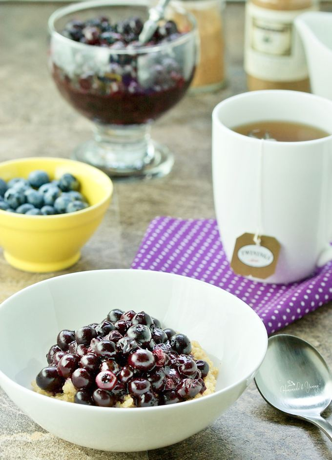 Blueberry breakfast bowl in the forefront, a cup of tea in the background.