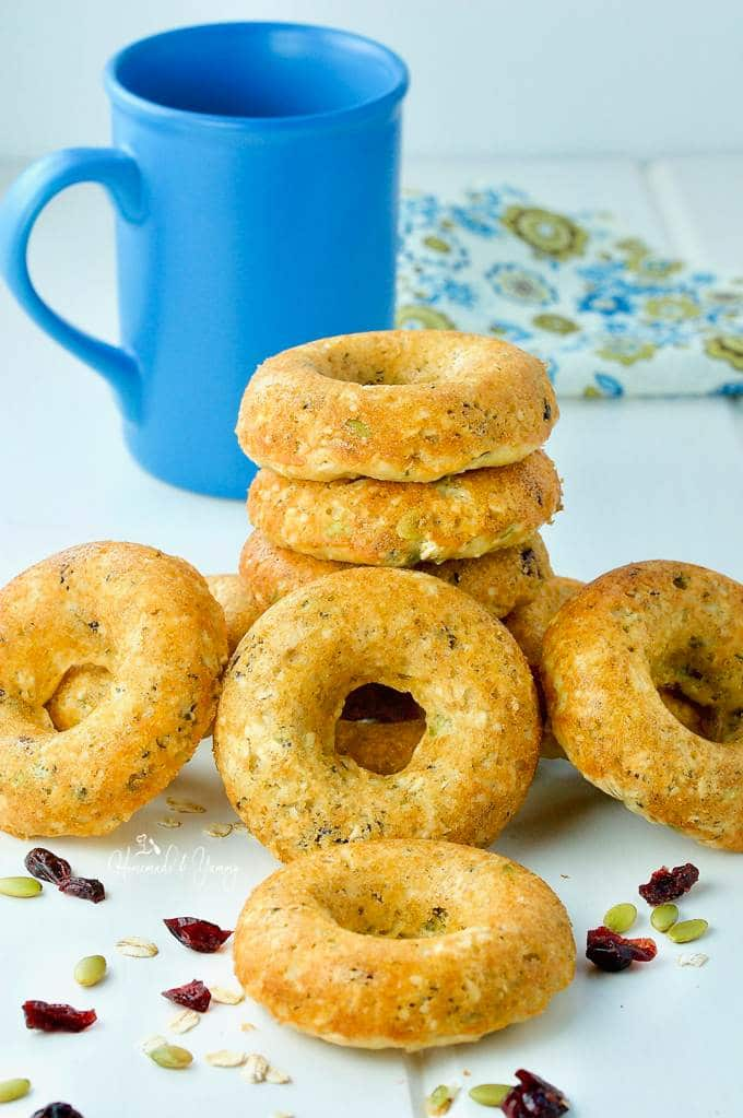 A pile of Oatmeal Breakfast donuts piled on the table with a blue coffee mug in the background.