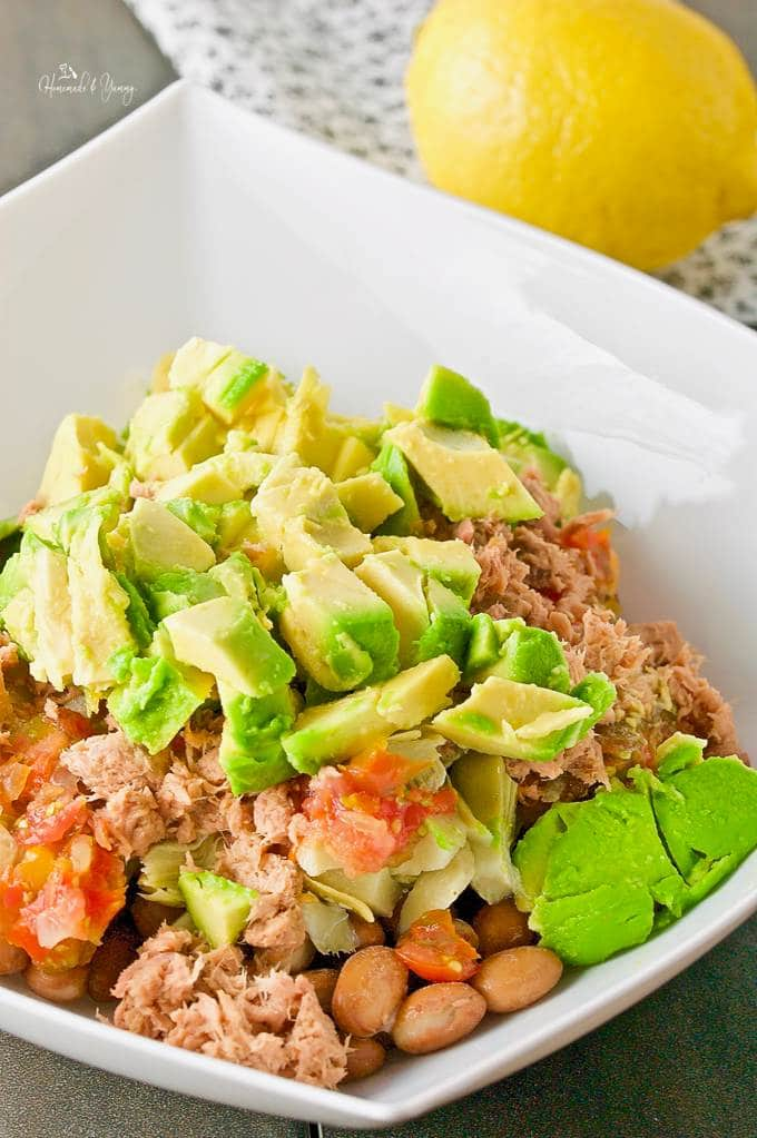 Close up of avocado, tuna and beans in a bowl ready to mix up with a lemon in the background.