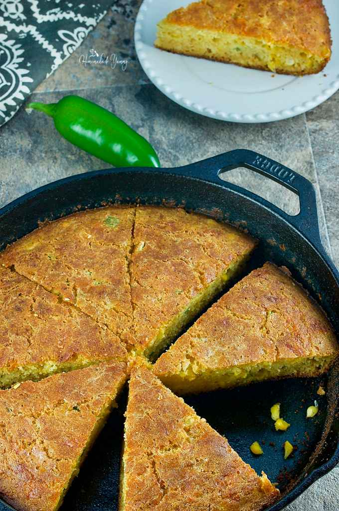 Overhead shot of cornbread cut into wedges in a cast iron pan.