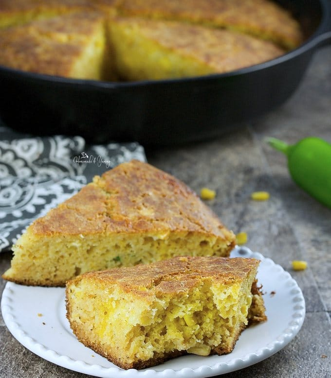 2 pieces of Cheezy Cornbread on a plate, one has a bite out of it.