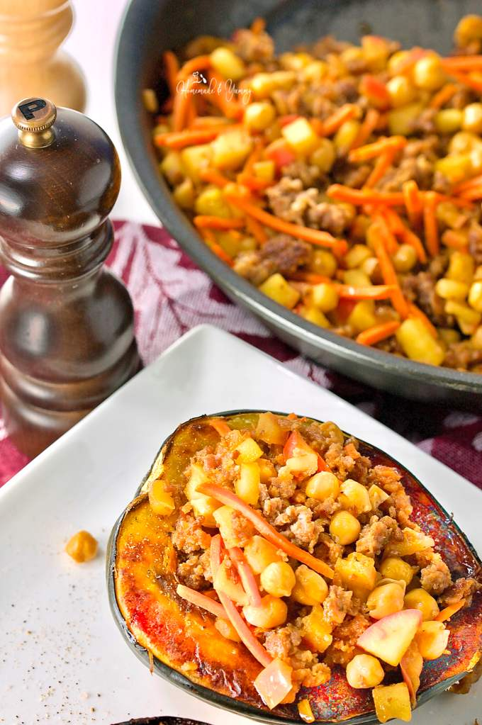 Sausage and apple stuffed squash on a plate, with addition stuffing in the background.