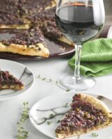 A piece of Pissaladiere French Pizza on a serving plate with a glass of wine.