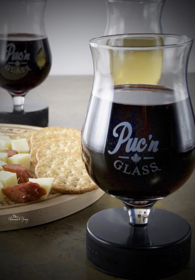 Puc'n GLASS filled with red wine, crackers and cheese in the background.