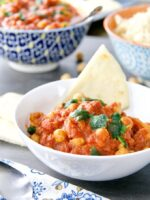 Close up of Chana Masala in a bowl with a piece of naan bread.